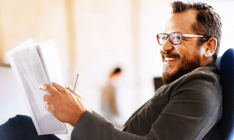 Man with glasses smiles while reading the paper
