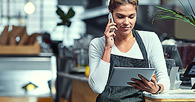 Female restaurant employee talking on a mobile phone while looking at a tablet.